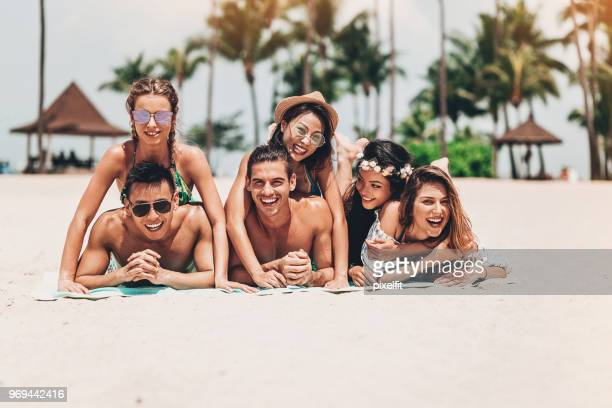young friends lying on the beach - medium group of people stock pictures, royalty-free photos & images