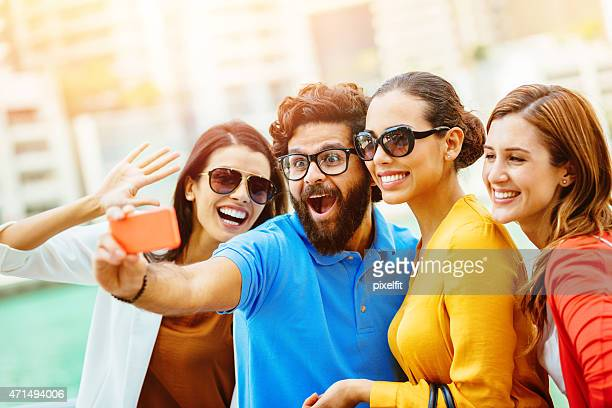 Young friends making selfie with smart phone outdoors