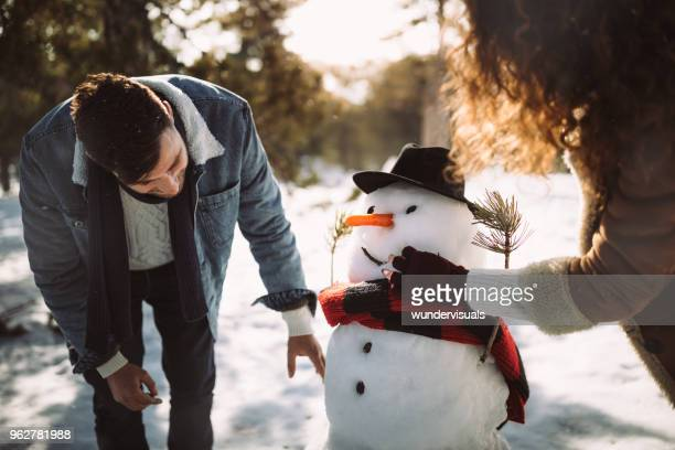 young friends making snowman in the snow in winter - snowman stock pictures, royalty-free photos & images