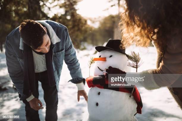jeunes amis faire des bonhomme de neige dans la neige en hiver - bonhomme de neige photos et images de collection