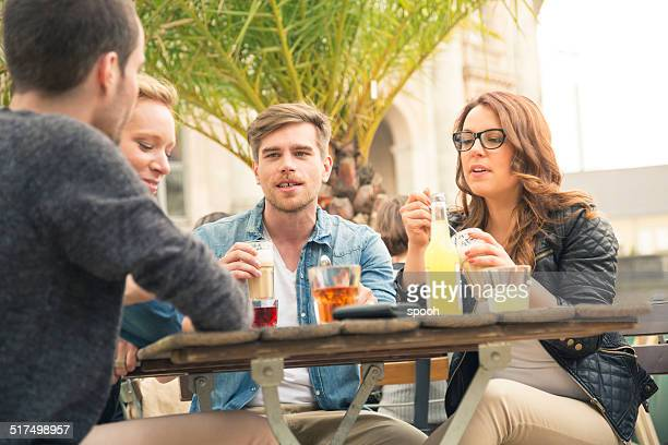 Young friends meeting and drinking in sidewalk cafe.