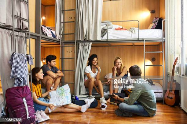 young friends planning trip in hostel - hostel stock pictures, royalty-free photos & images