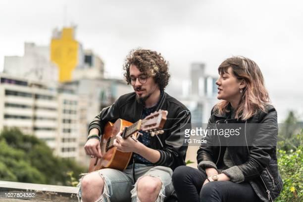 Jovens amigos tocando guitarra na cidade