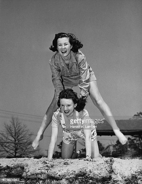 young friends playing leapfrog and smiling  - {{ contactusnotification.cta }} stockfoto's en -beelden