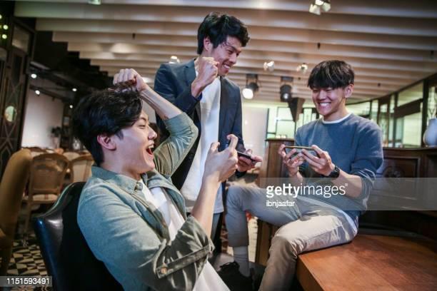 jonge vrienden spelen mobile game in café - sportwedstrijd stockfoto's en -beelden