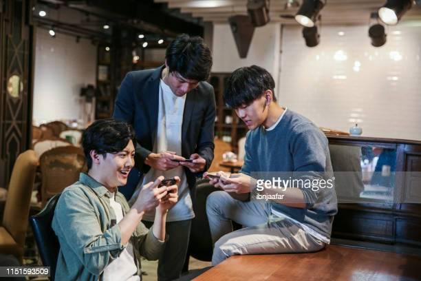 カフェでモバイルゲームをプレイしている若い友人 - 対戦試合 ストックフォトと画像
