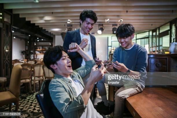 カフェでモバイルゲームをプレイしている若い友人 - 対戦 ストックフォトと画像