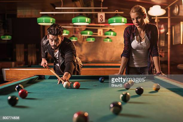 Young friends playing snooker in a pool hall.