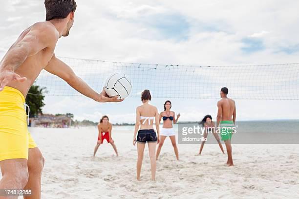 junge freunde spielen sie volleyball am strand. - strandvolleyball spielerin stock-fotos und bilder