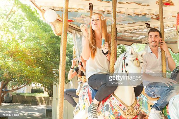 Young friends playing with soap sud riding carousel horses