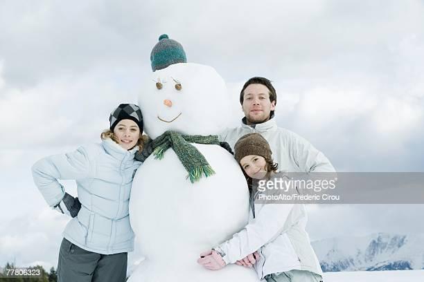 Young friends posing next to snowman, portrait