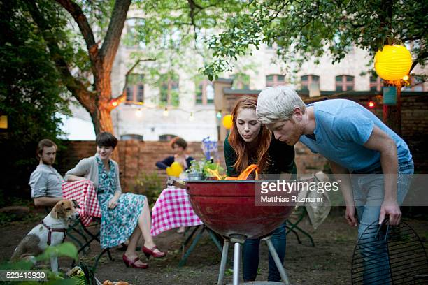 Young friends preparing barbecue grill at garden party