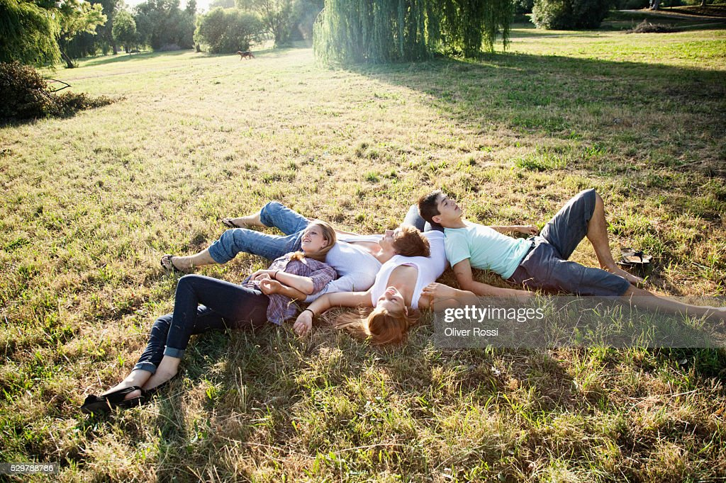 Young friends relaxing in the grass : Stockfoto