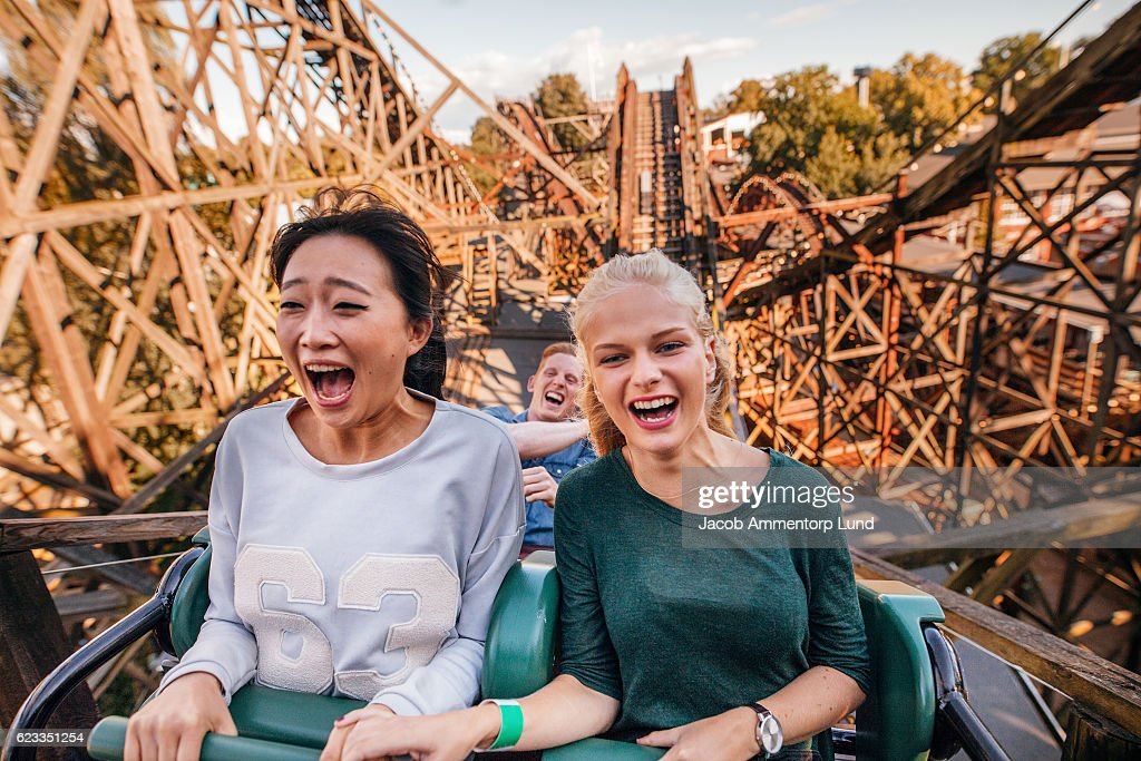 Young friends riding roller coaster ride : Stock Photo