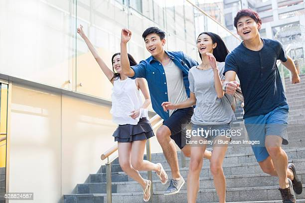 Young friends running down steps