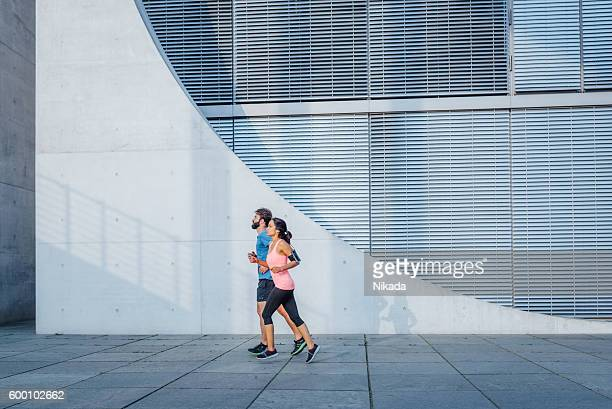 young friends running in front of wall - center athlete stock pictures, royalty-free photos & images