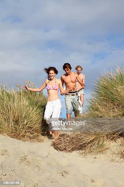 Junge Freunde laufen über Dünen