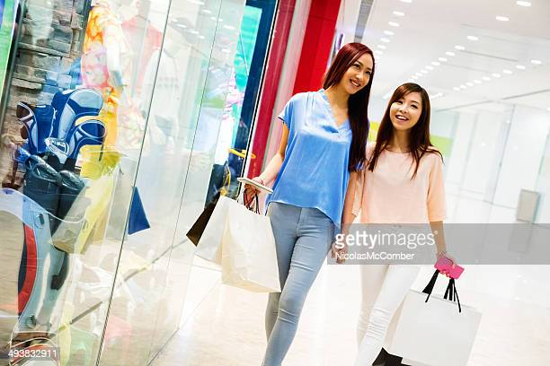 Young friends shopping holding hands