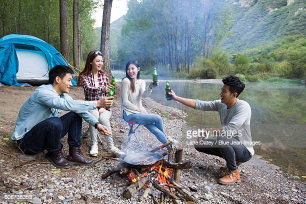 Young friends sitting around campfire drinking beer