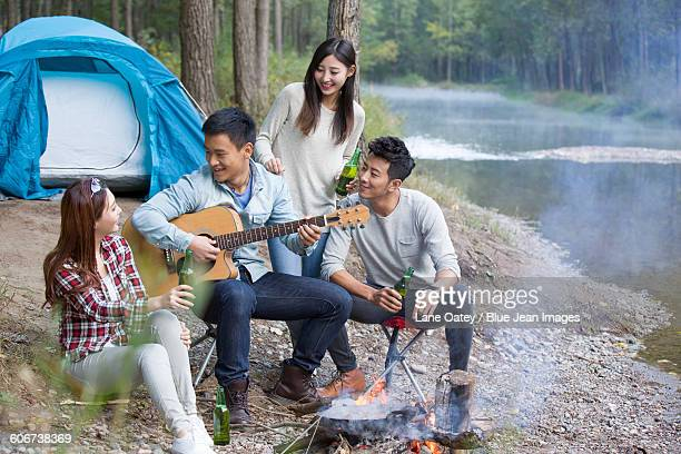 Young friends sitting around campfire playing guitar