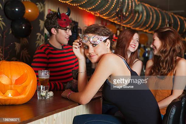young friends sitting in bar - naughty halloween stock photos and pictures