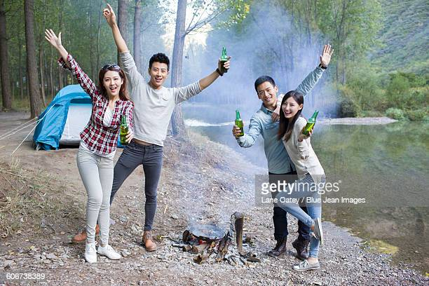 Young friends standing around campfire drinking beer
