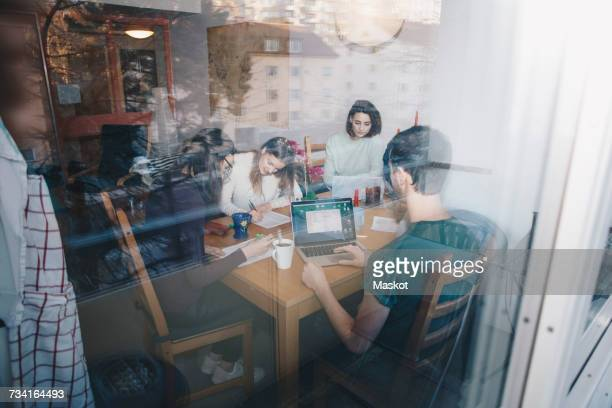 Young friends studying together in dorm room seen through glass window