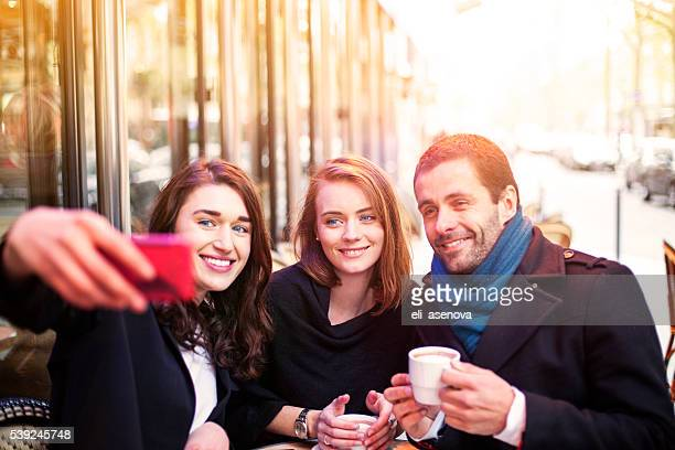 Young friends take selfie in a Paris bistro.