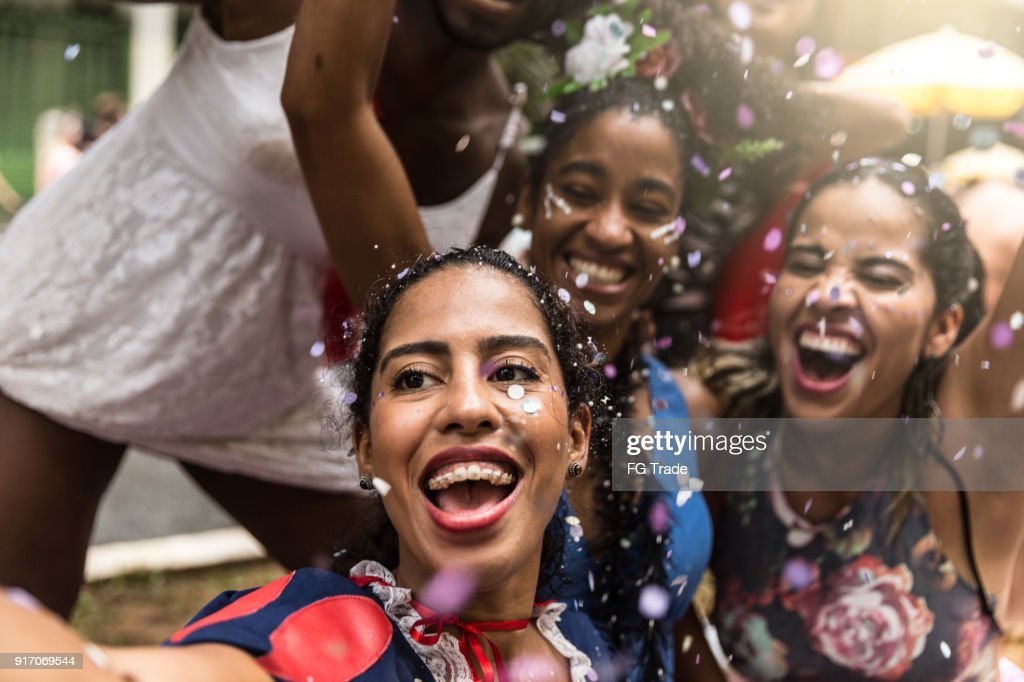Young friends taking selfies and having fun at the carnival street : Stock Photo