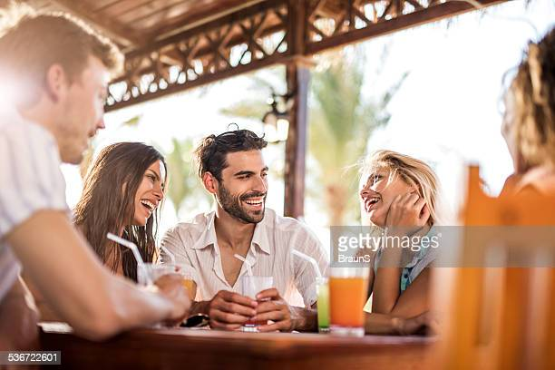 Young friends talking in a bar.