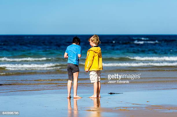 Young friends talking on a beach by the ocean.
