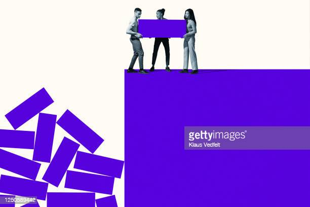 young friends throwing purple blocks from cliff - concept stock pictures, royalty-free photos & images