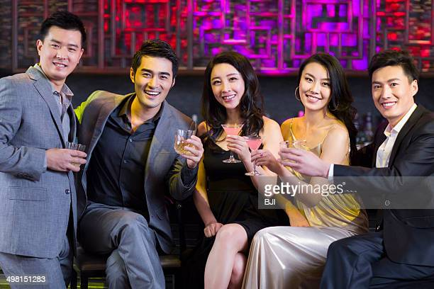Young friends toasting at bar