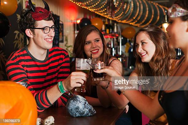 young friends toasting drinks in bar - naughty halloween stock photos and pictures