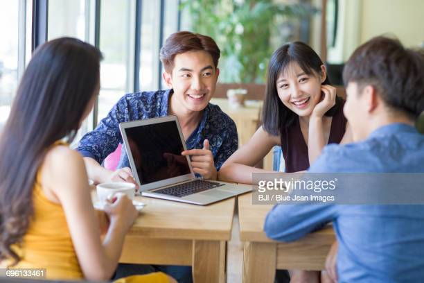 young friends using laptop in cafe - visual china group stock pictures, royalty-free photos & images
