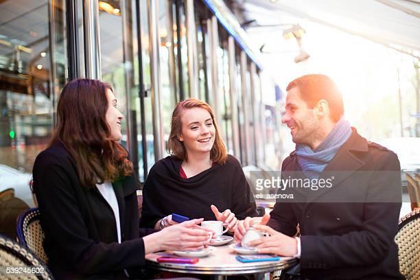 Jeunes amis à l'aide de la technologie dans un bistrot parisien.