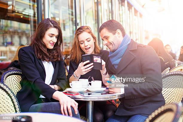 Young friends using technology in a Paris bistro.
