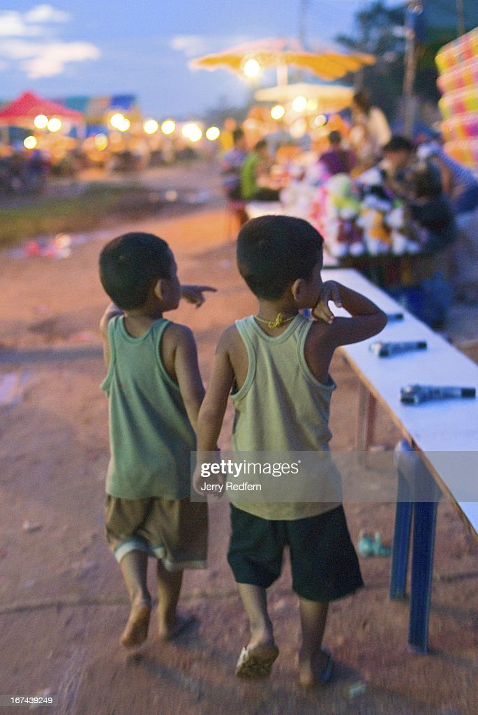 Young friends walk through the evening market along the Mekong riverfront in Vientiane. Throughout the country young children are left to themselves and are often found alone and in places where they would not be by themselves were they in the West..