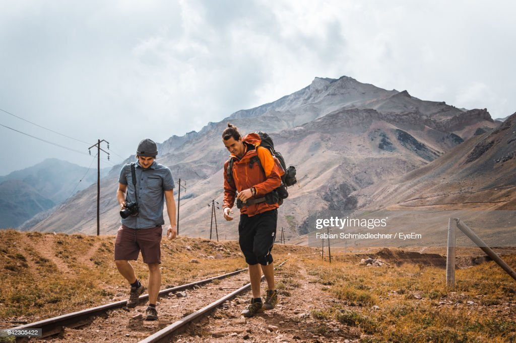 Young Friends Walking On Railroad Tracks Against Mountains : Stock Photo