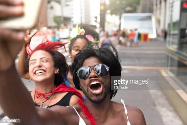 通りで selfie 写真を撮るカーニバル衣装を着て若い友人 - パレード ストックフォトと画像