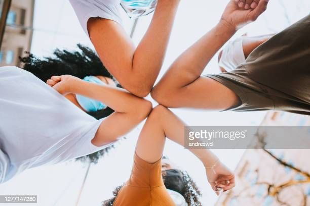 young friends wearing face mask doing new social distancing greet with elbows bumps for preventing coronavirus spread - bumpy stock pictures, royalty-free photos & images
