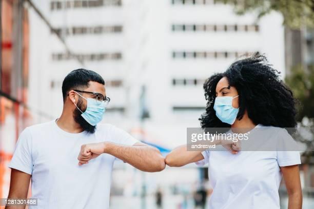 jovens amigos usando máscara fazendo novo distanciamento social saudação com cotovelo para prevenir surto de coronavírus - distância física e conceito de saudações de segurança - acenar - fotografias e filmes do acervo