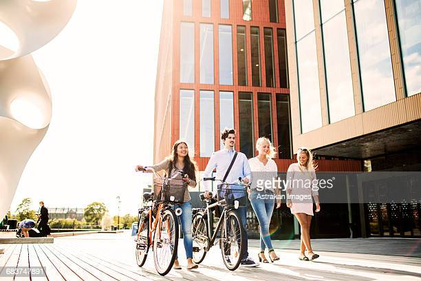 Young friends with bicycles walking outside concert hall in Malmo Live
