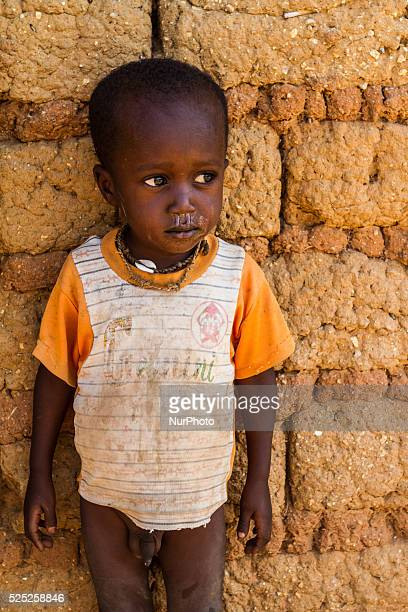 Young Fulani child in ragged clothing halfnaked poses by a traditional house near Kaduna Nigeria Photo Zsolt Repasy/NurPhoto