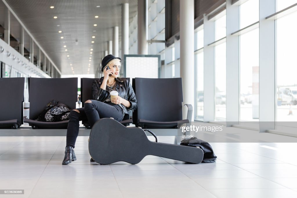 Young funky blond woman waiting for flight in airport lounge : Stock Photo