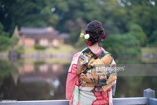 young furisode girl in japanese garden - seijin no hi stock pictures, royalty-free photos & images