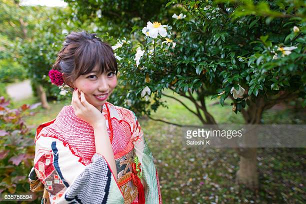 Young furisode girl in white camellia field