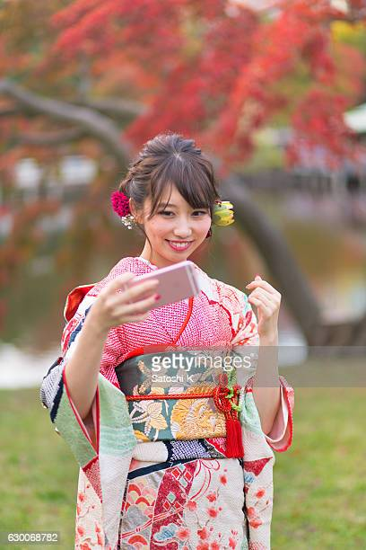young furisode girl taking selfie picture in autumn foliage - seijin no hi stock pictures, royalty-free photos & images