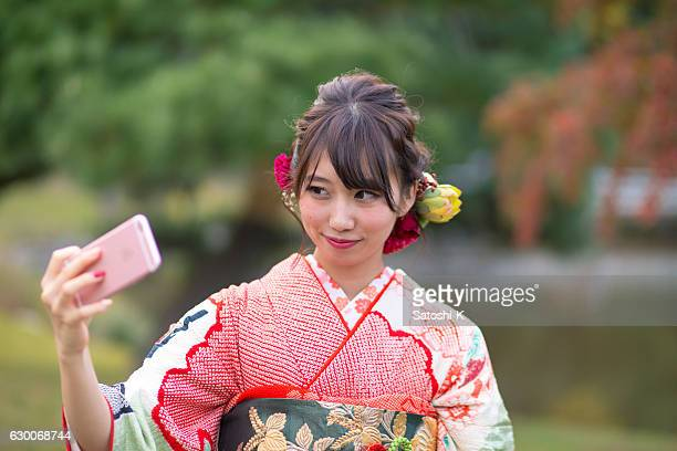 young furisode girl taking selfie picture in japanese garden - seijin no hi stock pictures, royalty-free photos & images