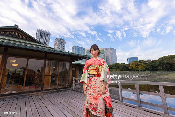 young furisode woman in japanese garden - seijin no hi stock pictures, royalty-free photos & images